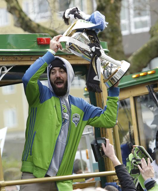Seattle Sounders forward Clint Dempsey holds up the the MLS Cup trophy for fans as he rides a trolly with teammates during a celebration march, Tuesday, Dec. 13, 2016, in Seattle. The Sounders def ...