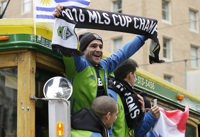 Seattle Sounders forward Nicolas Lodeiro, center, holds up a MLS Cup Champions scarf as he rides a trolly with teammates during a celebration march, Tuesday, Dec. 13, 2016, in Seattle. The Sounder ...