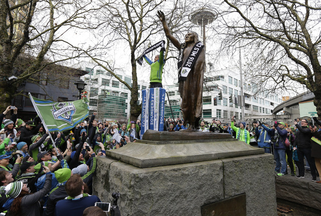 Seattle Sounders midfielder and captain Osvaldo Alonso holds up a MLS Cup Champions scarf as he stands next to a statue of Chief Seattle with the Space Needle in the background during a celebratio ...