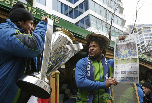 Seattle Sounders defender Roman Torres, right, holds an addition of the Seattle Times newspaper bearing his photo and a headline reference to his name as his teammate, forward Nelson Haedo Valdez, ...