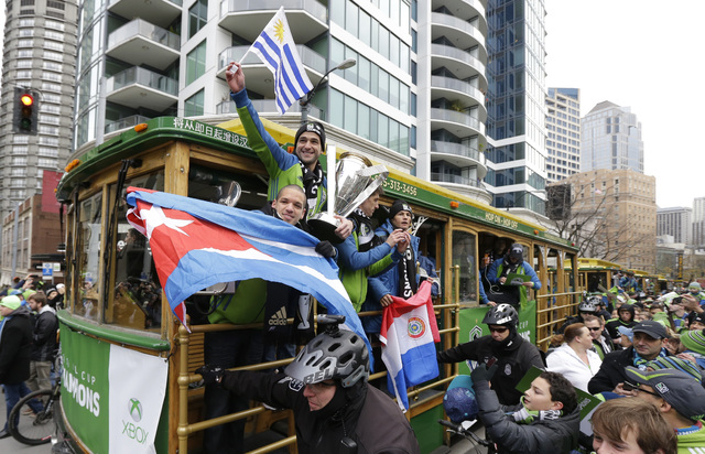 Seattle Sounders midfielder Osvaldo Alonso, left, holds the flag of his native Cuba, as forward Nicolas Lodeiro, top, holds the flag of his home country of Uruguay along with the MLS Cup trophy, a ...