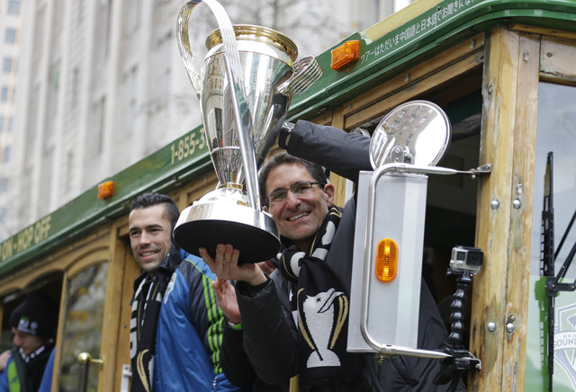 Seattle Sounders owner Adrian Hanauer, right, holds the MLS Cup trophy as he rides a trolly with his team during a celebration Tuesday, Dec. 13, 2016, in Seattle. The Sounders beat Toronto FC on D ...