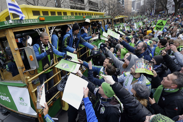 Seattle Sounders players, including captain Osvaldo Alonso, left, sign autographs for fans as they ride a trolly during a celebration Tuesday, Dec. 13, 2016, in Seattle. The Sounders beat Toronto  ...