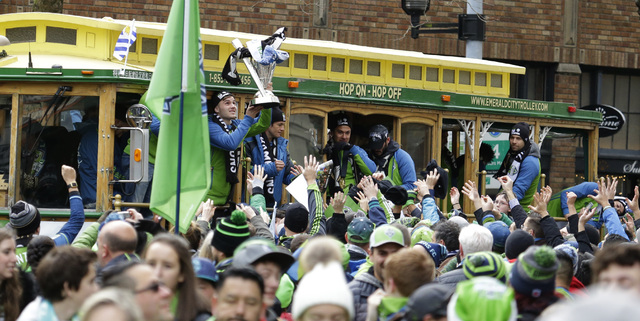 Seattle Sounders forward Jordan Morris, left, holds the MLS Cup trophy for fans as he rides a trolly with teammates during a celebration march, Tuesday, Dec. 13, 2016, in Seattle. The Sounders bea ...