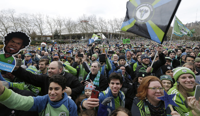 Seattle Sounders supporters wave flags and cheer during a celebration rally at the Seattle Center, Tuesday, Dec. 13, 2016, in Seattle. The Sounders beat Toronto FC on Dec. 10, 2016 to win the MLS  ...