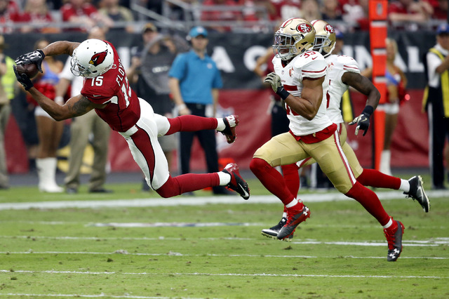 Arizona Cardinals wide receiver Michael Floyd (15) makes a diving catch as San Francisco 49ers free safety Eric Reid (35) defends during the first half of an NFL football game, Sunday, Nov. 13, 20 ...