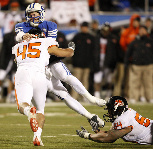 Oregon State linebacker David Paaluhi puts a hit on BYU quarterback Max Hall during the second half of the Las Vegas Bowl NCAA college football game in Las Vegas, Tuesday Dec. 22, 2009, won by BYU ...