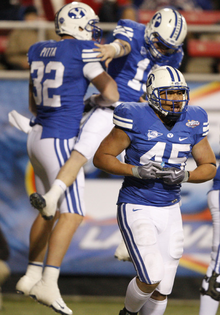 BYU's Harvey Unga (45) trots off the field as teammates Dennis Pitta (32) and Matt Marshall celebrate Pitta's third-quarter touchdown during the Las Vegas Bowl NCAA college football game in Las Ve ...