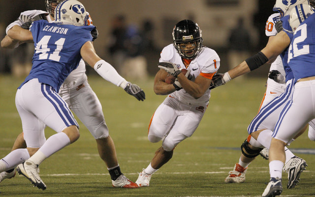 Oregon State running back Jacquizz Rodgers, center, finds a hole for a short gain against BYU during the first half of the Las Vegas Bowl NCAA college football game in Las Vegas, Tuesday Dec. 22,  ...