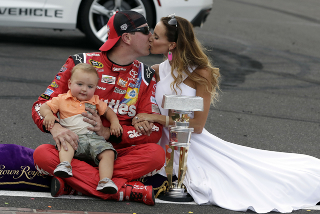 Kyle Busch kisses his wife Samantha as he holds their son Brexton after wining the Brickyard 400 NASCAR auto race at Indianapolis Motor Speedway in Indianapolis, Sunday, July 24, 2016. (AP Photo/R ...