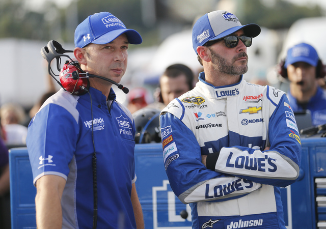 Jimmie Johnson, right, waits with crew chief Chad Knaus as they wait for NASCAR Sprint Cup qualifying at Richmond International Raceway in Richmond, Va., Friday, Sept. 9, 2016. (AP Photo/Steve Helber)