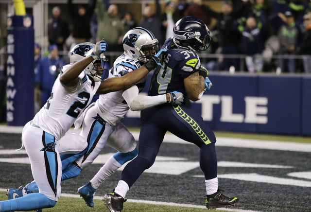 Seattle Seahawks' Thomas Rawls, right, pulls Carolina Panthers James Bradberry, left, and Daryl Worley into the end zone on a touchdown in the first half of an NFL football game, Sunday, Dec. 4, 2 ...