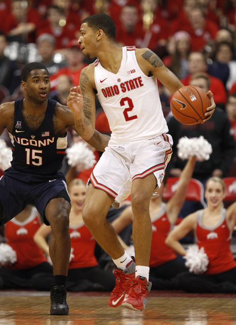 Ohio State forward Marc Loving, right, works against Connecticut guard Rodney Purvis during an NCAA college basketball game in Columbus, Ohio, Saturday, Dec. 10, 2016. Ohio State won 64-60. (Paul  ...