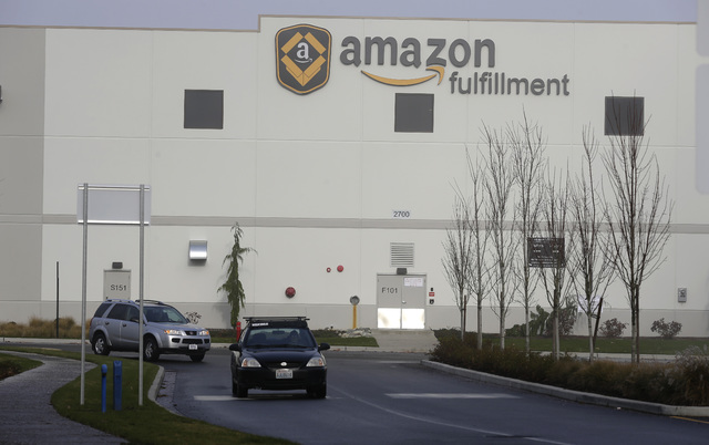 In this Nov. 30, 2015 file photo, cars drive away from Amazon.com's fulfillment center in DuPont, Wash.  (AP Photo/Ted S. Warren, file)