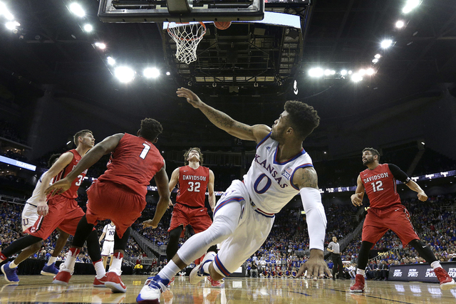 Kansas' Frank Mason III (0) watches his shot as he falls to the floor during the first half of an NCAA college basketball game against Davidson, Saturday, Dec. 17, 2016, in Kansas City, Mo. (Charl ...