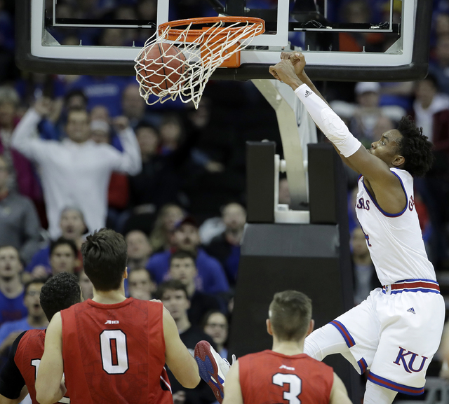 Kansas' Devonte' Graham, right, dunks the ball during the second half of an NCAA college basketball game against Davidson, Saturday, Dec. 17, 2016, in Kansas City, Mo. (Charlie Riedel/AP)