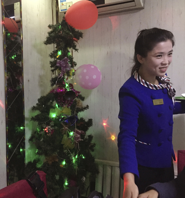 A waitress serves customers before a Christmas tree decorated with lights, ribbons and balloons in Pyongyang, North Korea. (AP Photo/Eric Talmadge)