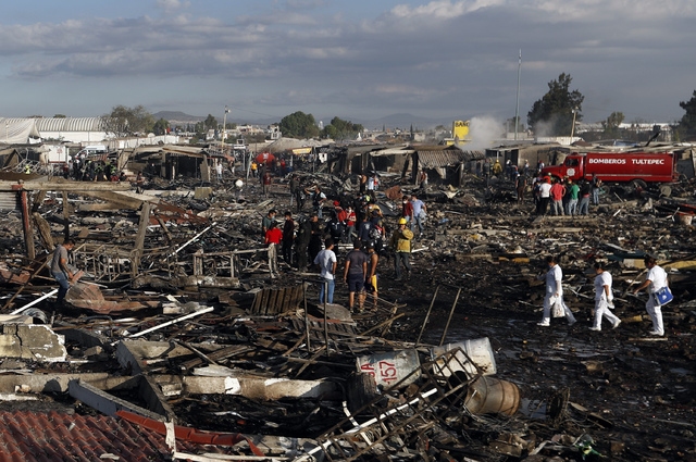 Firefighters and rescue workers walk through the scorched ground of Mexico's best-known fireworks market after an explosion explosion ripped through it, in Tultepec, Mexico, Tuesday, Dec. 20, 2016 ...