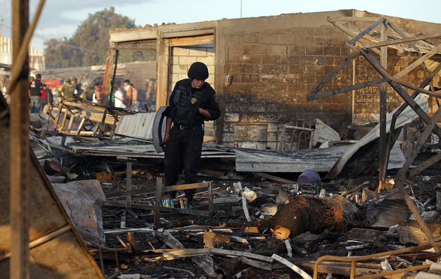 A Mexico State policeman looks through the scorched ground of the open-air San Pablito fireworks market, in Tultepec, outskirts of Mexico City, Mexico, Tuesday, Dec. 20, 2016. (AP Photo/Eduardo Ve ...