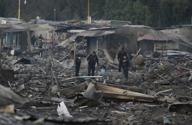 Local policemen walk through the scorched ground of the open-air San Pablito fireworks market, in Tultepec, outskirts of Mexico City, Mexico, Tuesday, Dec. 20, 2016. (AP Photo/Eduardo Verdugo)