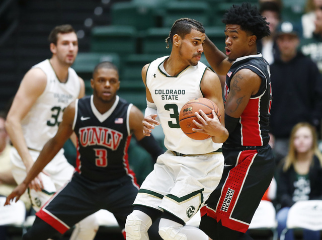 Colorado State guard Gian Clavell, center, is caught with the ball as UNLV forward Tyrell Green, left, and guard Jovan Mooring defend during the first half of an NCAA college basketball game Wedne ...