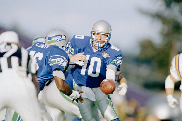 Seattle Seahawks quarterback Dan McGwire (10) hands the ball off to Lamar Smith during the third quarter of their pre-season game against the Minnesota Vikings in Husky Stadium in Seattle, Aug. 20 ...