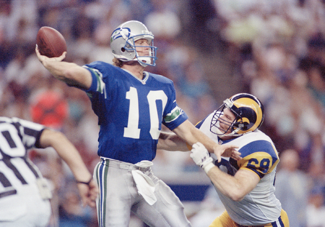 Quarterback Dan McGwire (10) of the Seattle Seahawks manages to get the pass off in time to avoid the sack as Jim Skow (68) of the Los Angeles Rams applies the defensive rush during the fourth qua ...
