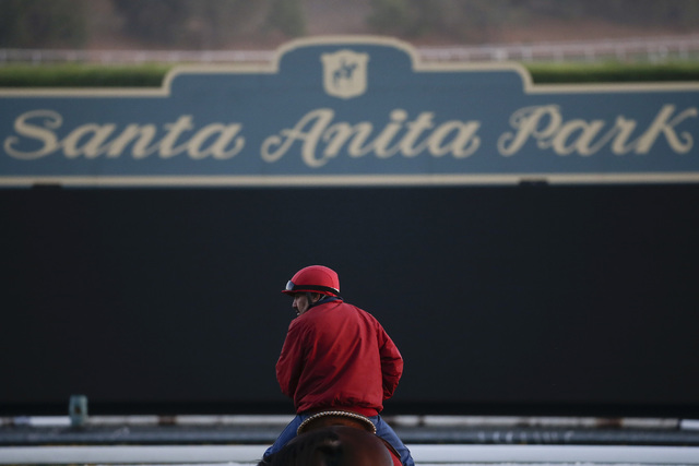 An outrider stands in front of a sign on the track as horses train for the Breeders' Cup races at Santa Anita Park Wednesday, Oct. 29, 2014, in Arcadia, Calif. (AP Photo/Jae C. Hong)