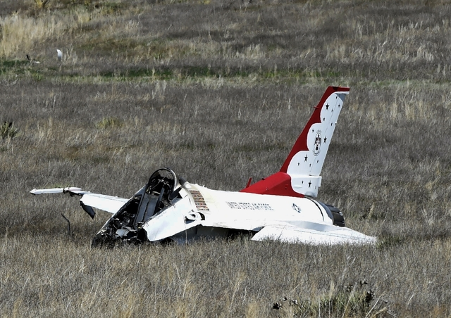 A U.S. Air Force Thunderbird that crashed following a flyover rests on the ground south of the Colorado Springs, Colo., airport after a performance at a commencement for Air Force Academy cadets T ...