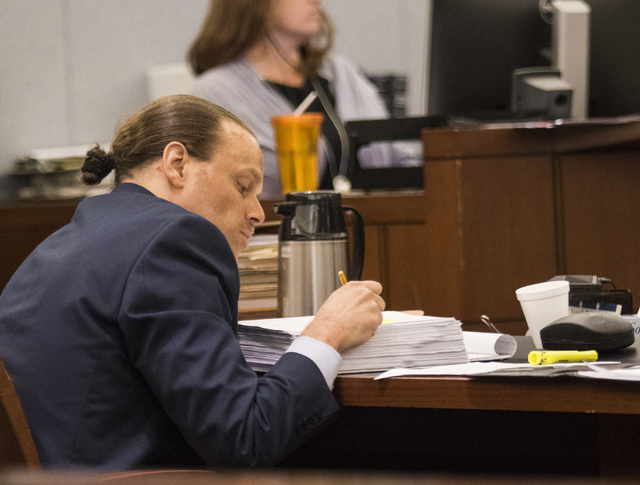 Defendant Norman Belcher looks over his notes during his death penalty trial at the Regional Justice Center in Las Vegas, on Friday, Dec. 2, 2016. Belcher, 41, is charged with killing his grade-sc ...