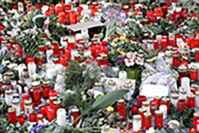 Candles burn between flowers in Berlin, Germany, Wednesday, Dec. 21, 2016, two days after a truck ran into a crowded Christmas market nearby and killed several people. (Michael Sohn/AP)