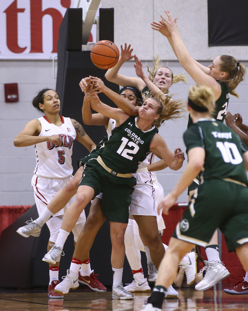 Colorado State guard/forward Callie Kaiser (12) fights for a rebound against UNLV players, including UNLV forward Simone Sheppard (5), during a basketball game at Cox Pavilion in Las Vegas on Thur ...