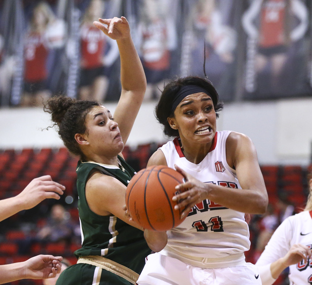 UNLV guard Dylan Gonzalez (11) looks for an open shot as Colorado State guard/forward Myanne Hamm (21) defends during a basketball game at Cox Pavilion in Las Vegas on Thursday, Dec. 29, 2016. UNL ...