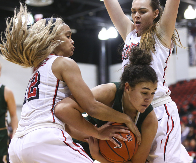 UNLV guard Dakota Gonzalez (12) and forward Alyssa Anderson (20) fight for possession of the ball against Colorado State guard/forward Myanne Hamm (21) during a basketball game at Cox Pavilion in  ...