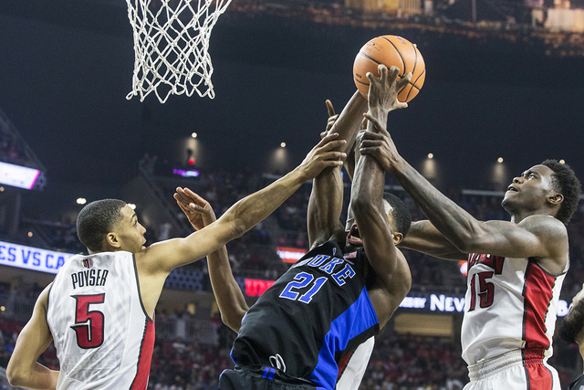 Duke's Amile Jefferson (21) fights for a rebound with UNLV's  Jalen Poyser (5) and Dwayne Morgan (15) during the Blue Devils road matchup with the Rebels at T-Mobile Arena on Saturday, Dec. 10, 20 ...