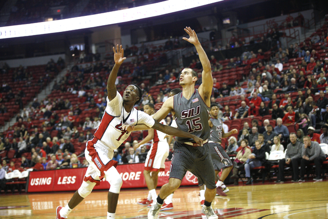 UNLV Rebels guard Kris Clyburn (1)and Southern Illinois Salukis forward Austin Weiher (15) reach to catch the ball during a game at the Thomas & Mack Center on Monday, Dec. 19, 2016, in Las Ve ...