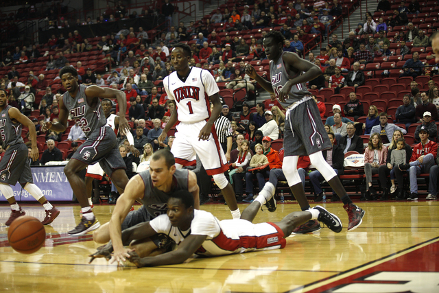 Southern Illinois Salukis forward Austin Weiher (15) and UNLV Rebels forward Cheickna Dembele (11) dive for the ball during a game at the Thomas & Mack Center on Monday, Dec. 19, 2016, in Las  ...