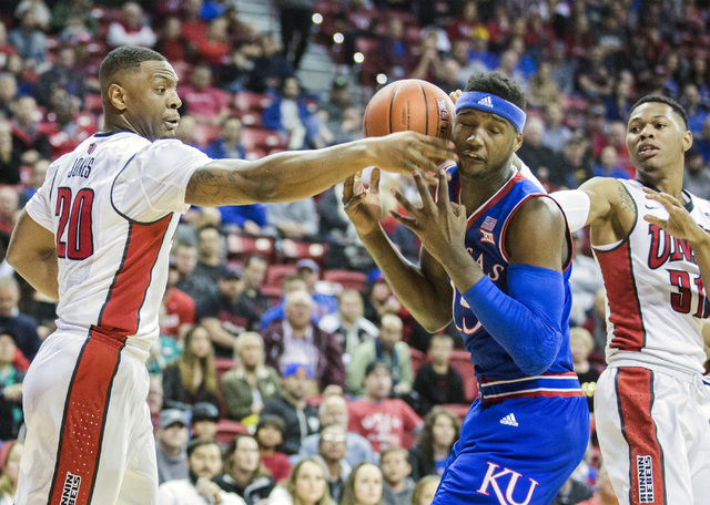 UNLV forward Christian Jones and Kansas Jayhawks forward Carlton Bragg fight for a rebound during first half action at the Thomas and Mack Center on Thursday, Dec. 22, 2016. Kansas defeated the Re ...