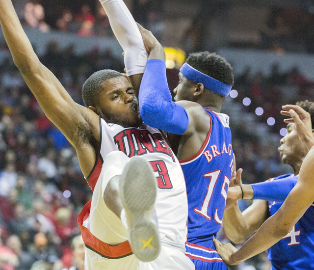 UNLV forward Tyrell Green collides with Kansas Jayhawks forward Carlton Bragg during first half action at the Thomas and Mack Center on Thursday, Dec. 22, 2016. Kansas defeated the Rebels, 71-53.  ...