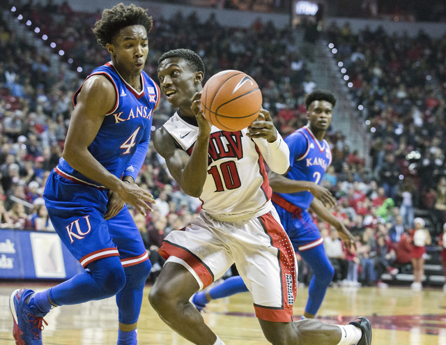 UNLV guard Zion Morgan drives on Devonte' Graham during the first half against the Kansas Jayhawks at the Thomas and Mack Center on Thursday, Dec. 22, 2016. Kansas defeated the Rebels, 71-53. (Jef ...