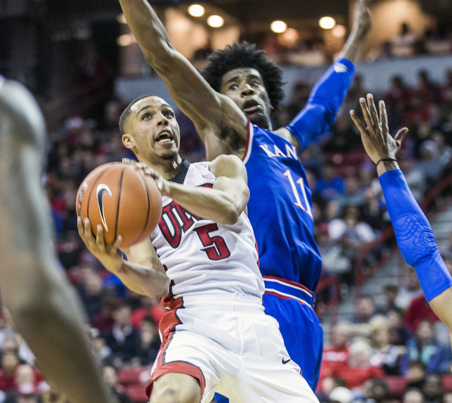 UNLV guard Jalen Poyser drives on Kansas Jayhawks guard Josh Jackson during second half action at the Thomas and Mack Center on Thursday, Dec. 22, 2016. Kansas defeated the Rebels, 71-53. (Jeff Sc ...