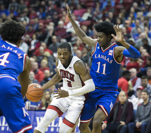 UNLV forward Tyrell Green drives around Kansas Jayhawks guard Josh Jackson during second half action at the Thomas and Mack Center on Thursday, Dec. 22, 2016. Kansas defeated the Rebels, 71-53. (J ...