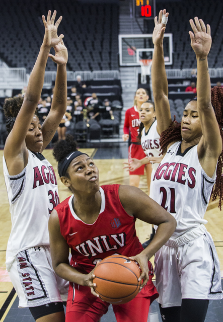 UNLV's Jordyn Bell (23) shoots over New Mexico State's   Gia Pack (30) and Tamera William (21) during the Play4Kay Shootout at T-Mobile Arena on Tuesday, Dec. 20, 2016, in Las Vegas. Benjamin Hage ...