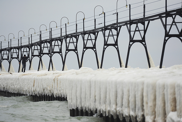 A man walks along the ice covered pier at the South Haven Lighthouse on Saturday, Dec. 24, 2016, in South Haven, Mich. (Don Campbell/AP)
