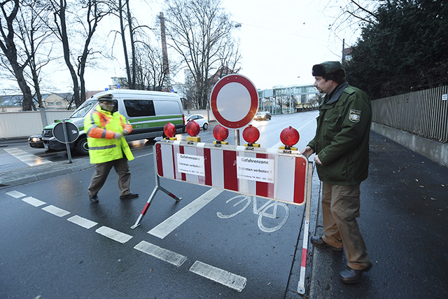 Policemen blocked a road in Augsburg, Germany, Sunday, Dec. 25, 2016. Thousands temporarily left Christmas presents and decorations behind while authorities disarmed a World War II bomb. The bomb  ...
