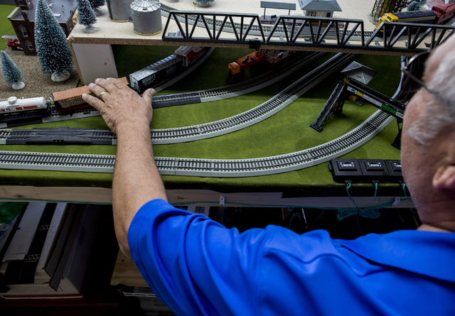 Jim Henry, a 61-year-old retired Air Force Security Police tech sergeant, conducts his freelance Pennsylvania Railroad model train set in his North Las Vegas homeTuesday, Dec. 13, 2016. (Elizabeth ...
