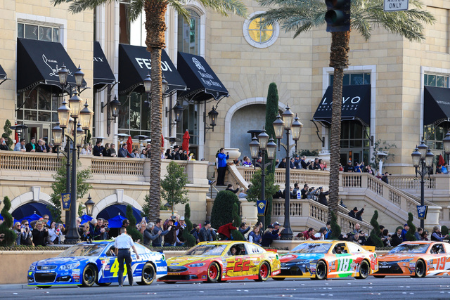 Drivers Jimmy Johnson (41), Joey Logano (22), Kyle Busch (18) and Carl Edwards (19) wait their turn to do a burnout on Las Vegas Boulevard during the NASCAR Victory Lap in Las Vegas on Thursday, D ...