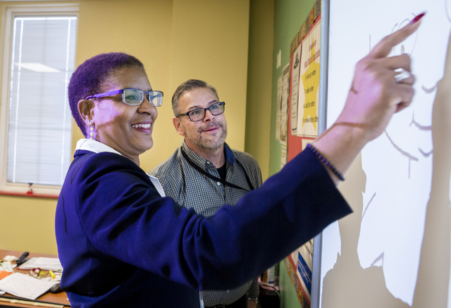 Principal Rachelle Conner, left, and Victor Portalatin, Spanish teacher, draws a portrait of herself while kids name in Spanish each part of the face drawn, at the 100 Academy of Excellence, 2341  ...