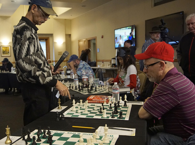 Las Vegas Chess Center member Timothy McCarthy, 55, looks on as Virgil Reyes moves a chess piece for Timur Gareyev, a chess grandmaster who broke the world record for simultaneous chess games play ...