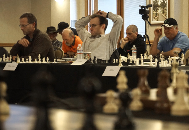 Chess players wait to play their next move against chess grandmaster Timur Gareyev, who broke the world record for simultaneous chess games played blindfolded at the UNLV Foundations Building in L ...